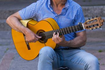 Mężczyzna grający na gitarze na ulicy