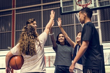 Group of teenager friends on a basketball court giving each other a high five Fototapete