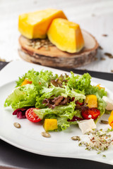 European Italian salad of lettuce, cherry tomatoes, pumpkin, edible pumpkin flowers, and pumpkin seeds, in a white plate. Copy space, selective focus