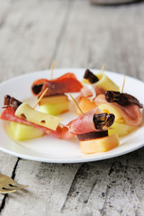 Grasshoppers wrapped with salami and proscuitto and served with cheese and melons.