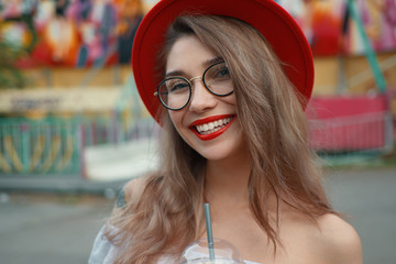 Cheerful young woman holding a drink while smiling