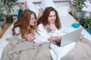 Two young women in bed with laptop in white interior Two young women in a bed with a laptop in a white interior. They watch the show, laugh, talk, shop, eat breakfast