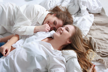 Two girlfriends laughing and hugging in bed in the morning at home.