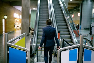 Businessman walking with luggage towards escalator