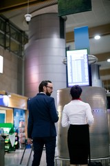Businessman and woman looking at departure board