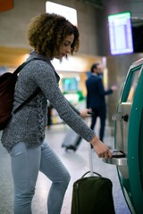 Woman using airline ticket machine