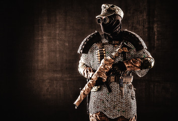 Post apocalyptic soldier in black mask and glasses, wool field cap and handmade armor from car tires and hauberk, standing at attention with submachine gun on shoulder, black background studio shoot