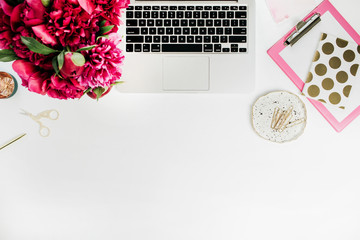 Flat lay workspace with laptop, accessories and peony flower bouquet on white background. Top view blog hero header.