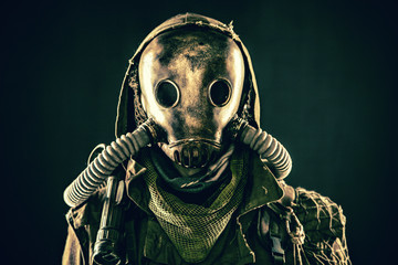 Close up portrait of nuclear post-apocalypse survivor, living underground mutant or creature, skilled stalker wearing rags and armored full-face gas mask or air breathing apparatus, toned shoot Wall mural