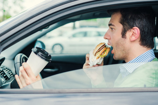 Hungry man driving his car while eating food in the traffic