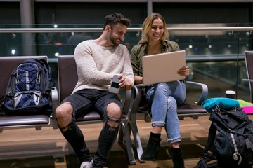 Couple using laptop in waiting area