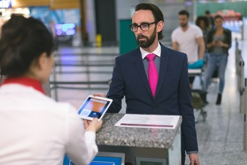 Airline check-in attendant checking ticket of commuter on