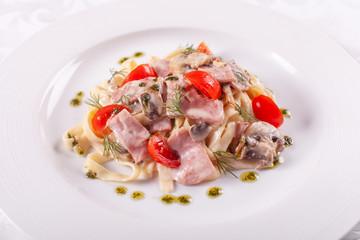 tagliatelle with mushrooms . Italian Pasta on white plate with champignons, ham and tomato