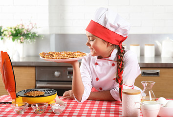 Little girl looks at the plate of freshly made waffles
