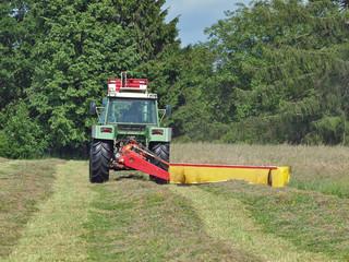 Bauer auf dem Traktor bei der Heuernte