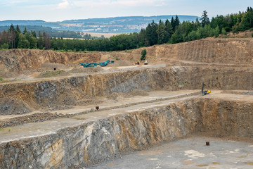 Opencast mining quarry with lots of machinery. Mining in the granite quarry. Working mining machine - digger, drilling machine. Mining industry. Wall mural
