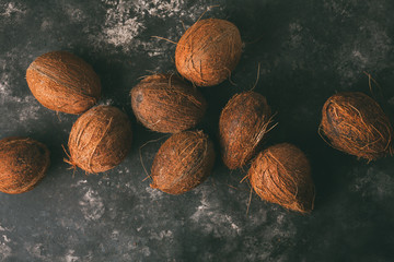 Pile of coconuts on a dark background.