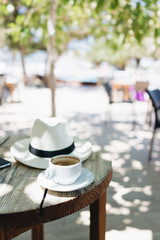 Coffee cup and a hat on the wooden table outside on a sunny day
