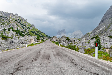 Empty deserted road in leading to menacind stormy, cloudy rocky mountains in the Dolomites, Italy
