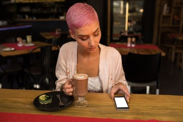 Woman using mobile phone while having chocolate milkshake at