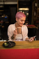 Woman using smartphone while having chocolate milkshake in restaurant