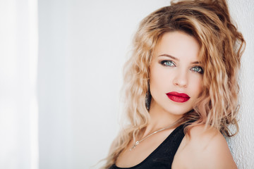 Studio portrait of stunning sensual blonde woman with wavy hair and professional make-up with red plump lips leaning on white wall. Isolate on white. Copyspace.
