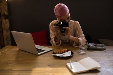 Stylish woman taking picture of breakfast with camera