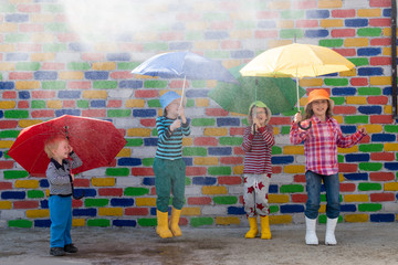 Happy children in colorful hats are sheltered from the rain under multicolored umbrellas in front of mottled brick wall. Fun during the summer holidays. Boys and girl have funny time. Copy space