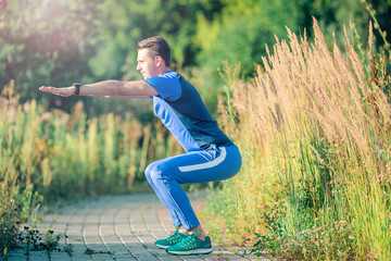 Sportive young man doing sport exercises outdoors in the park