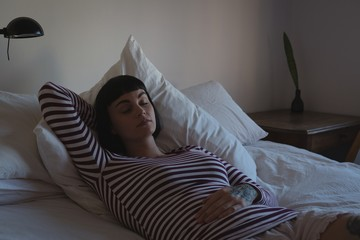 Woman relaxing in bedroom at home