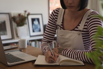 Woman writing on a diary at home