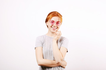 Attractive young woman with long red hair, wearing pink cat eye sunglasses, showing flirtatious body language, touching face. Beautiful redhead female flirty facial expression. Background, copy space.