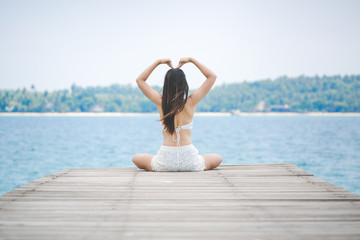 Woman making heart sign on bridge