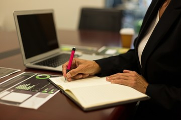 Mature businesswoman writing in diary on desk