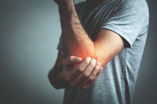 Caucasian man with elbow pain. Pain relief concept