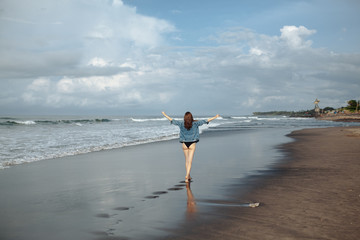 Happy smile brunette Woman wearing black swimsuit and denim jacket at ocean background enjoy walking at beach, hands raised up to the sky. Freedom concept
