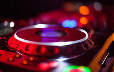 bokeh of DJ turntable and music deck illuminated at night with colourful lights lighting
