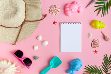 Baby girls' things for the beach. Straw hat, shorts, sunglasses, block with flippers, toys for sand on a pink background. View from above