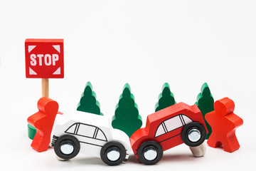 Wooded toy car are crashed. Accident road traffic with wooden toy cars in the town on white background, safety and traffic regulations concept, backgrounds.Transportation system concept.