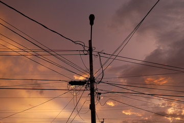 A street light post and power lines are seen at sunset during a blackout in Maracaibo