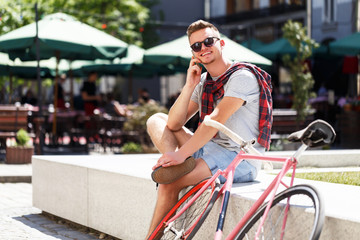 Handsome young hipster man sitting near the bicycle and using smartphone in the sunny street