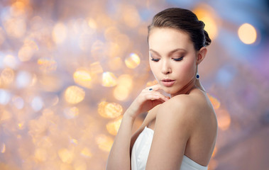 beauty, jewelry, people and luxury concept - beautiful asian woman or bride with earring and finger ring over holidays lights background