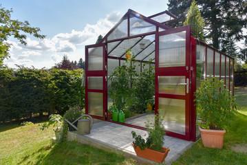 Ein rotes Gewächshaus im Garten