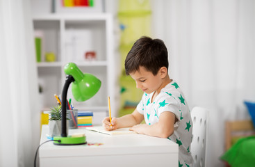 education, childhood and school concept - little boy sitting at desk and writing to notebook at home