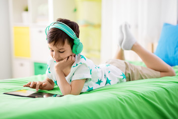 childhood, technology and people concept - smiling boy with tablet pc computer and headphones lying on bed at home