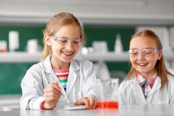 education, science, chemistry and children concept - kids or students making chemical experiment at school laboratory