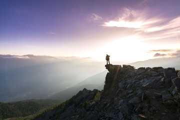 Young man standing on the Top of the mountain and enjoying total freedom during sunset in South Tyrol