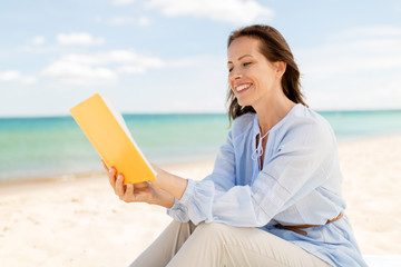 people and leisure concept - happy smiling woman reading book on summer beach