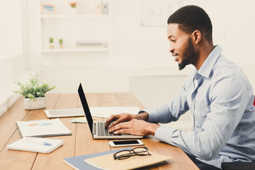 Young black businessman working with laptop