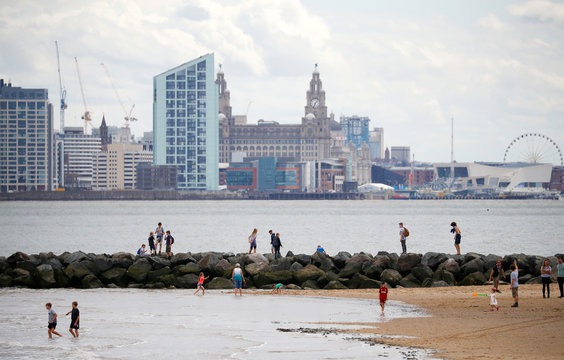 People enjoy the beach, as Liverpool's skyline is seen in the background, in New Brighton